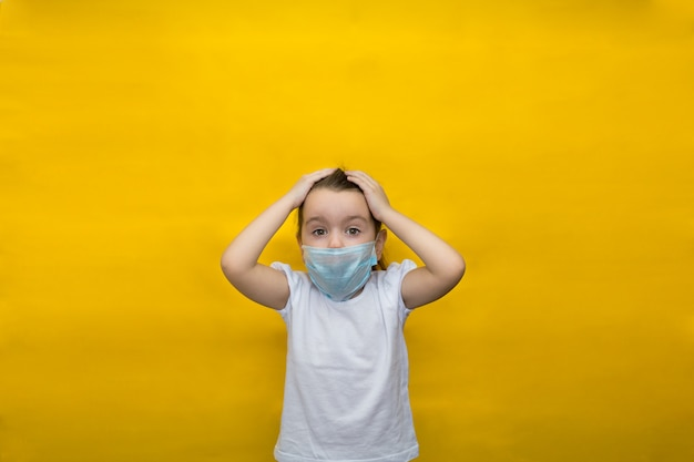 Little girl in a protective mask holds her head in fear isolated on a yellow wall. protection against coronavirus