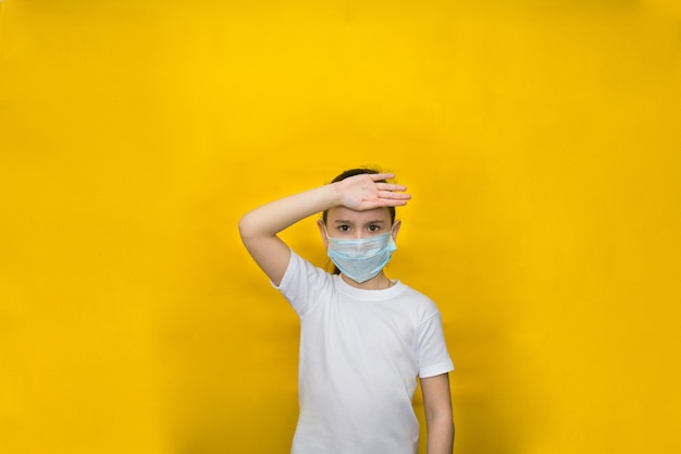 Little girl in a protective mask measures the temperature her hand on a yellow wall protection against coronavirus