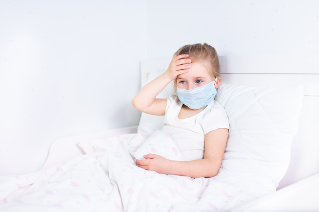 Little girl in protective medical mask staying in bed and touching her head. headache, migraine, feaver concept.