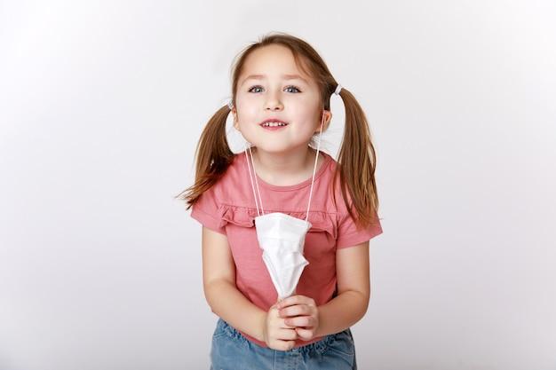 Маленькая девочка снимает медицинскую маску от вирусов и бактерий