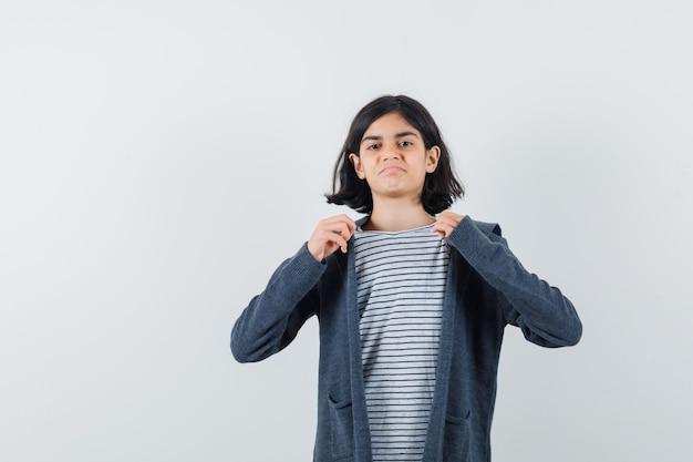 Маленькая девочка тянет воротник ее футболки в куртке и смотрит гордо.