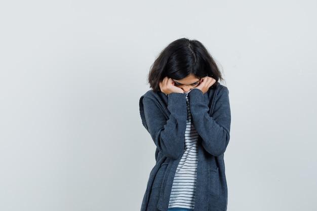 Tシャツ、ジャケット、動揺して顔に襟を引っ張る少女
