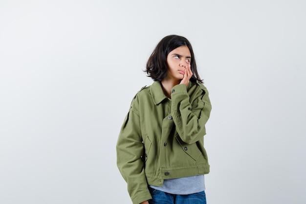 Bambina che tira giù la palpebra con il dito in cappotto, t-shirt, jeans e sembra stanca. vista frontale.