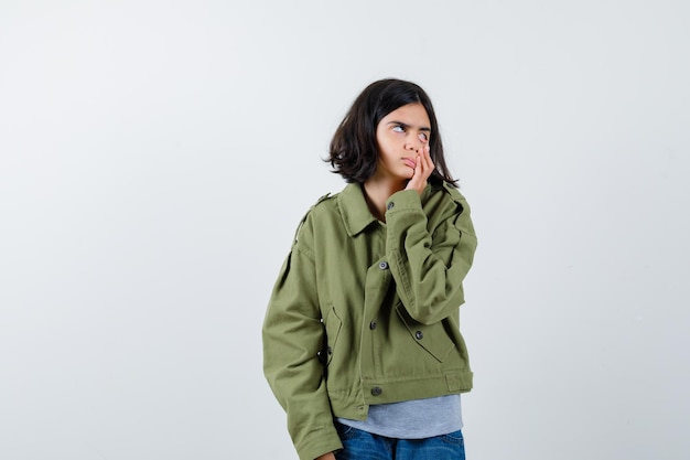 Маленькая девочка опускает веко пальцем в пальто, футболке, джинсах и выглядит усталой. передний план.