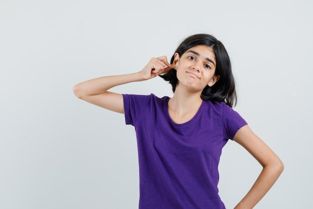 Bambina che tira giù il lobo dell'orecchio in maglietta e sembra confusa