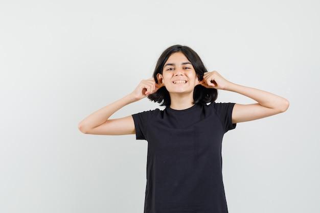 Маленькая девочка опускает мочки ушей в черной футболке и выглядит забавно, вид спереди.