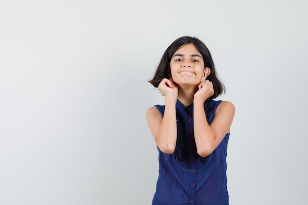 Маленькая девочка опускает мочки ушей в синей блузке