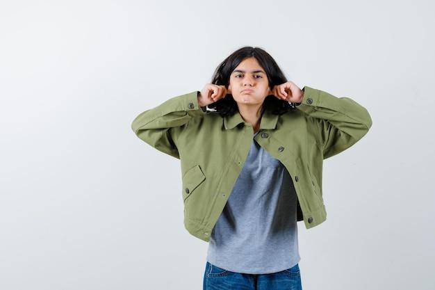 Bambina che tira i lobi delle orecchie mentre soffia le guance in cappotto, t-shirt, jeans e sembra divertente. vista frontale.