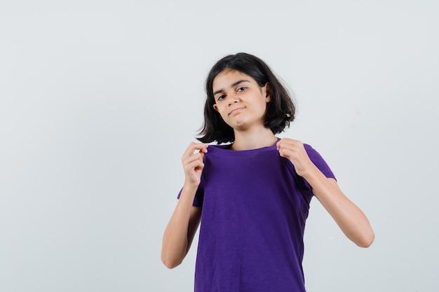 어린 소녀 t- 셔츠에 그녀의 칼라를 당기고 자랑스럽게보고