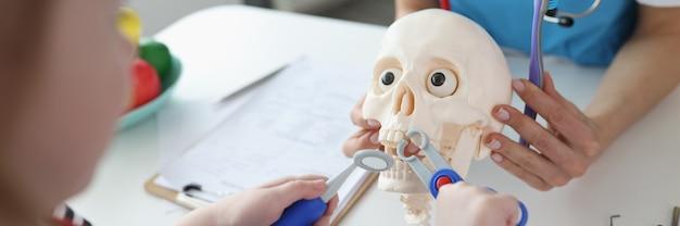 Маленькая девочка вытаскивает зуб из искусственного черепа с детскими стоматологическими инструментами крупным планом
