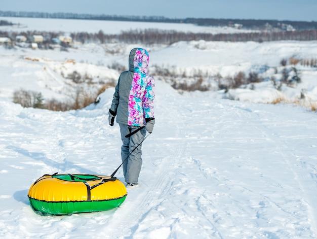 Маленькая девочка тянет трубки для зимней горки на холме
