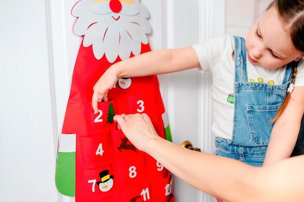 Маленькая девочка достает дома подарок из красного адвент-календаря