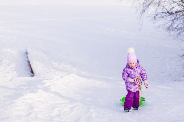 Little girl pulls a sled in warm winter day
