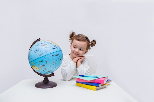 Little girl pupil looks lovingly at a globe on a white isolated