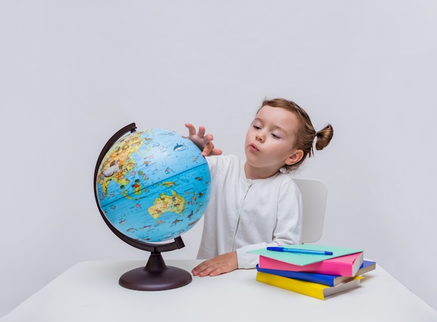 A little girl pupil sits at a table and studies a globe on a white isolated