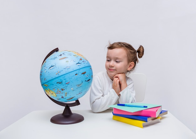 A little girl pupil sits at a table with a globe and books and looks at the camera on a white isolated