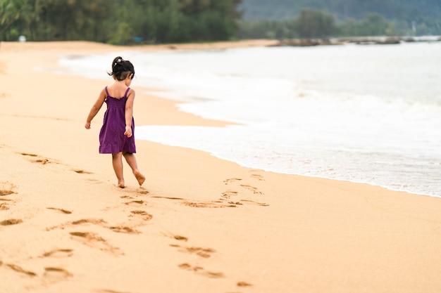 Little girl in purple dress walking on the seashore.