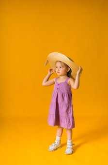 A little girl in a purple sundress and a straw hat on a yellow surface with space for text