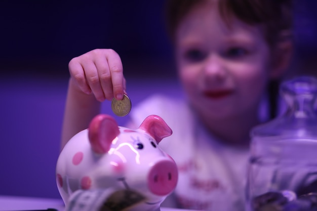 Little girl puts coin in piggy bank on table