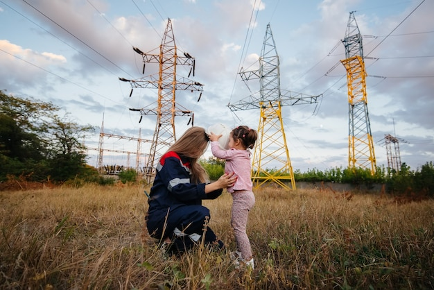 A little girl puts on a helmet for her mother to an engineering worker. concern for future generations and the environment. energy.