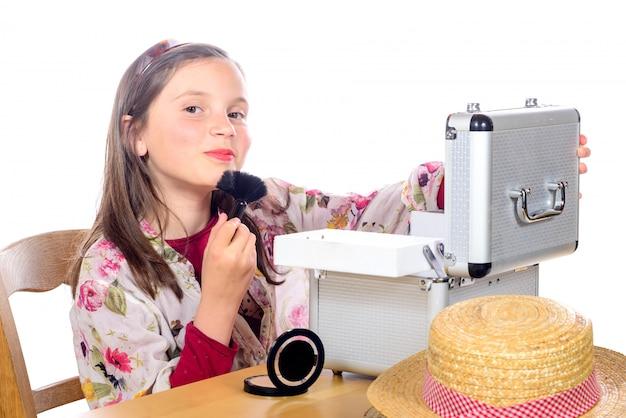 A little girl puts makeup