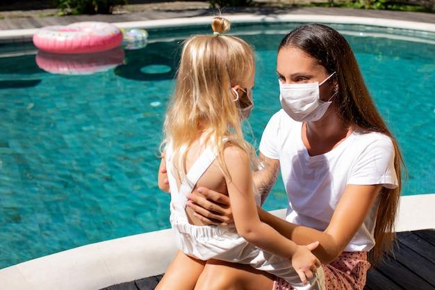 Маленькая девочка надевает маску для мамы. фото высокого качества