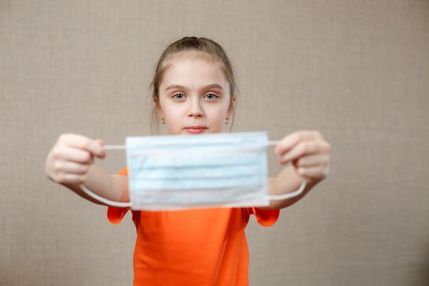 Маленькая девочка надевает на лицо медицинскую маску против бактерий и вирусов. выборочный фокус.