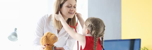 어린 소녀는 박제 장난감 소아과 작업을 들고 소아과 의사에 청진기를 넣습니다.