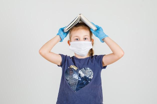 Bambina che mette libro sulla sua testa in maglietta, guanti e maschera vista frontale.