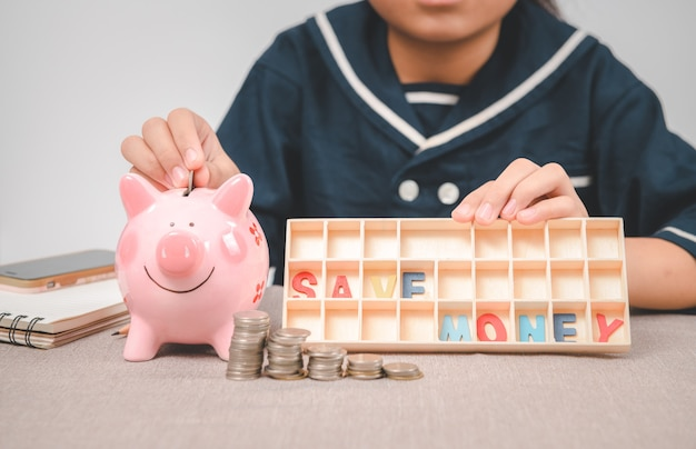 Little girl  putting coin from piggy bank on table