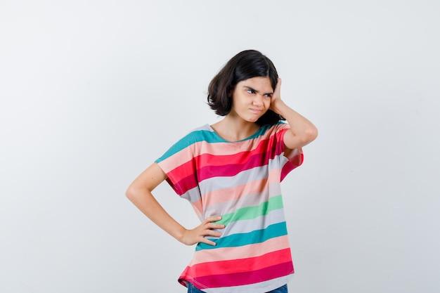 Bambina che mette la mano sulla testa mentre tiene la mano sulla vita, distoglie lo sguardo in maglietta e sembra pensierosa, vista frontale.