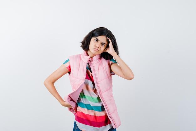 Bambina che mette la mano sulla vita mentre si gratta la faccia in maglietta, giubbotto imbottito, jeans e sembra dispiaciuta, vista frontale.