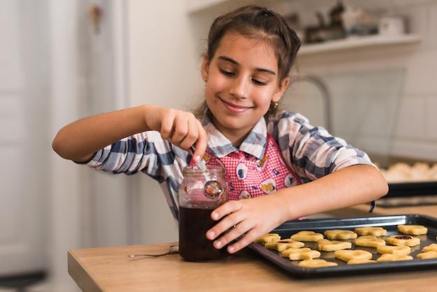 小さな女の子がおいしいクッキーに蜂蜜を入れて、朝食の準備をしています。