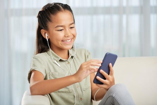自宅で携帯電話を使ってヘッドホンをつけて音楽を聴く少女