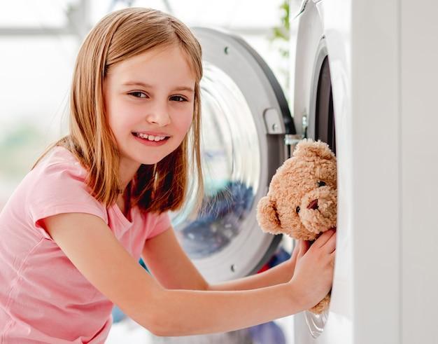 Маленькая девочка кладет плюшевую игрушку в открытую стиральную машину и улыбается