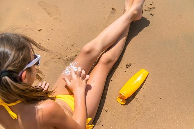 ビーチの砂の上に日焼け止めクリームを置く少女
