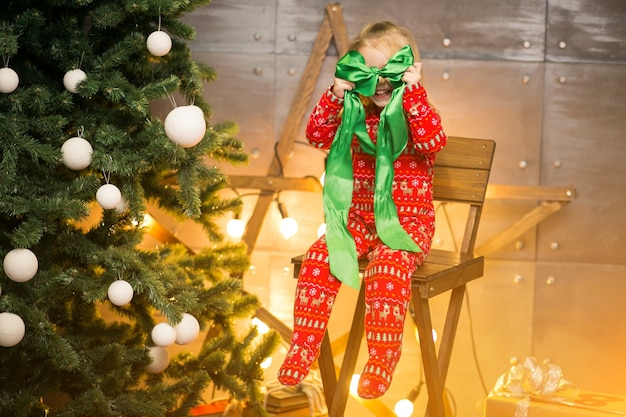 Little girl in pyjamas by the christmas tree on a wooden chair
