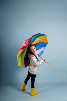 A little girl in a raincoat and yellow rubber boots holds a multi-colored umbrella on a blue background with a copy of the space