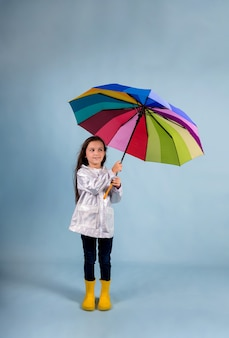 A little girl in a raincoat and yellow rubber boots stands and holds a multi-colored umbrella on a blue background with a place for text