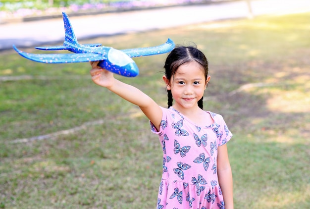 Little girl raise up a blue toy airplane