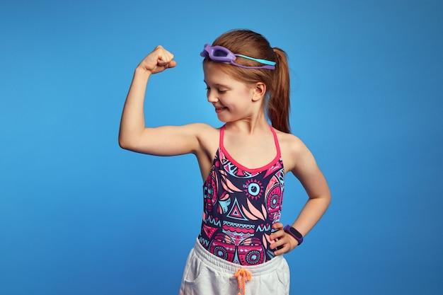 Маленькая девочка поднимает руку и, глядя на мышцы, носит очки и купальник