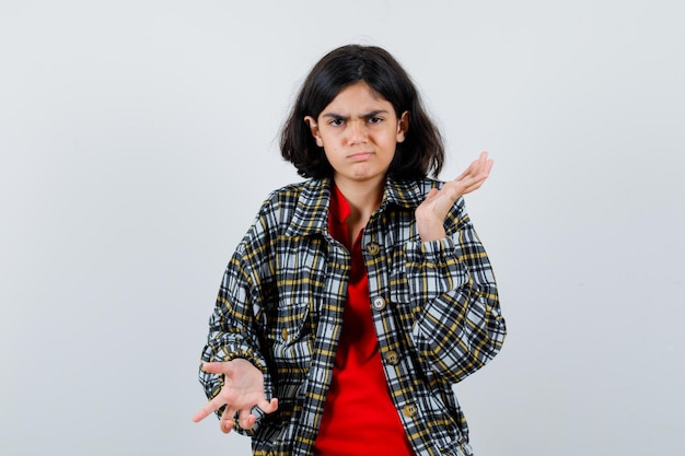 Little girl raising arms with aggressive manner in shirt,jacket and looking anxious. front view.