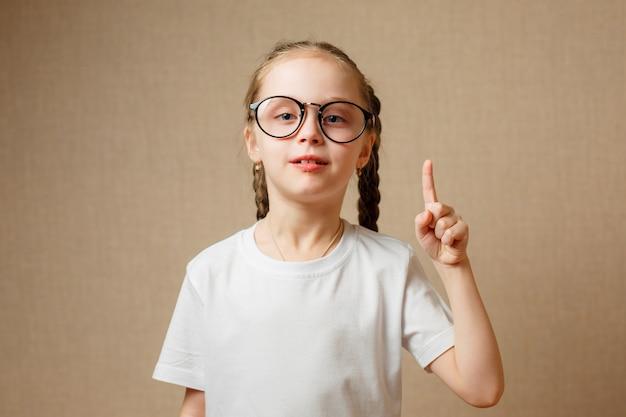 面白い注意ジェスチャーで指を上げる少女