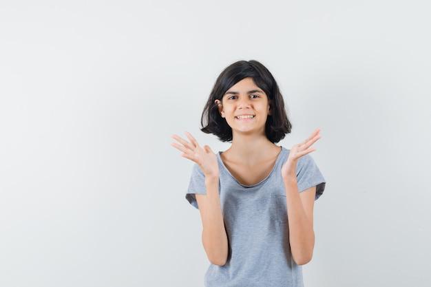 Маленькая девочка поднимает руки в футболке и выглядит веселой. передний план.