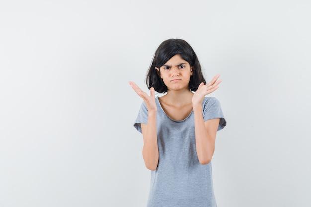 Tシャツで手を上げて物思いにふける少女、正面図。
