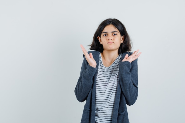 Bambina che solleva le mani in gesto perplesso in maglietta