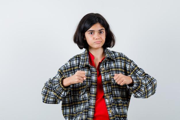 Маленькая девочка поднимает кулаки в рубашке, куртке и выглядит готовой. передний план.