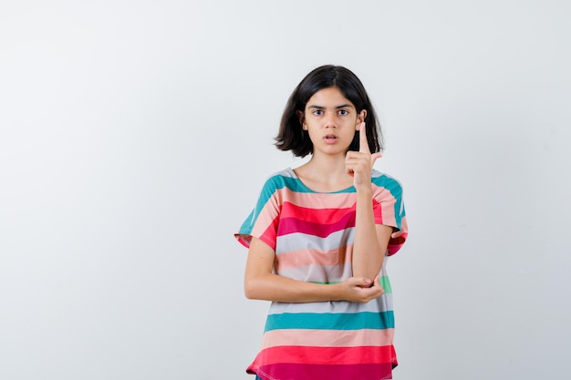 Bambina che alza il dito indice nel gesto di eureka mentre tiene la mano sul gomito in maglietta e sembra sensata. vista frontale.