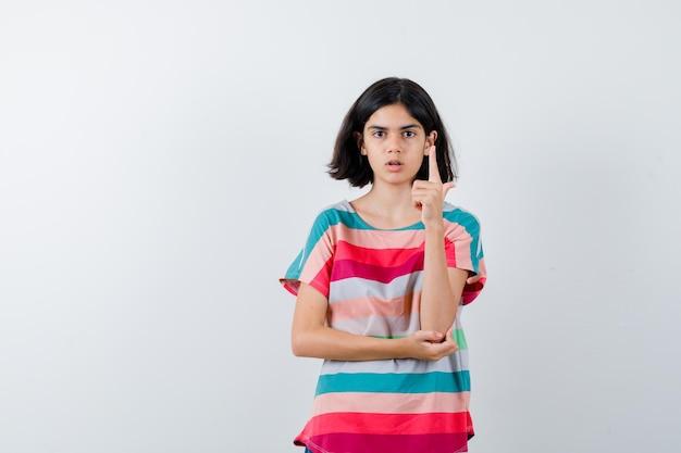 어린 소녀는 티셔츠에 팔꿈치에 손을 잡고 현명하게 보이는 동안 유레카 제스처로 검지 손가락을 올립니다. 전면보기.
