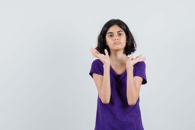 Bambina che alza le palme aperte in maglietta e sembra confusa